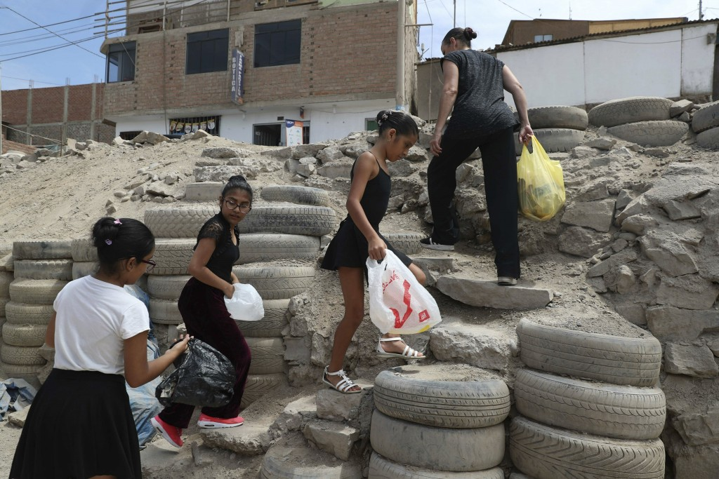 In this April 4, 2019 photo, Maria del Carmen Silva, a former professional dancer, and her ballet students, search and collect recycling plastic bottl