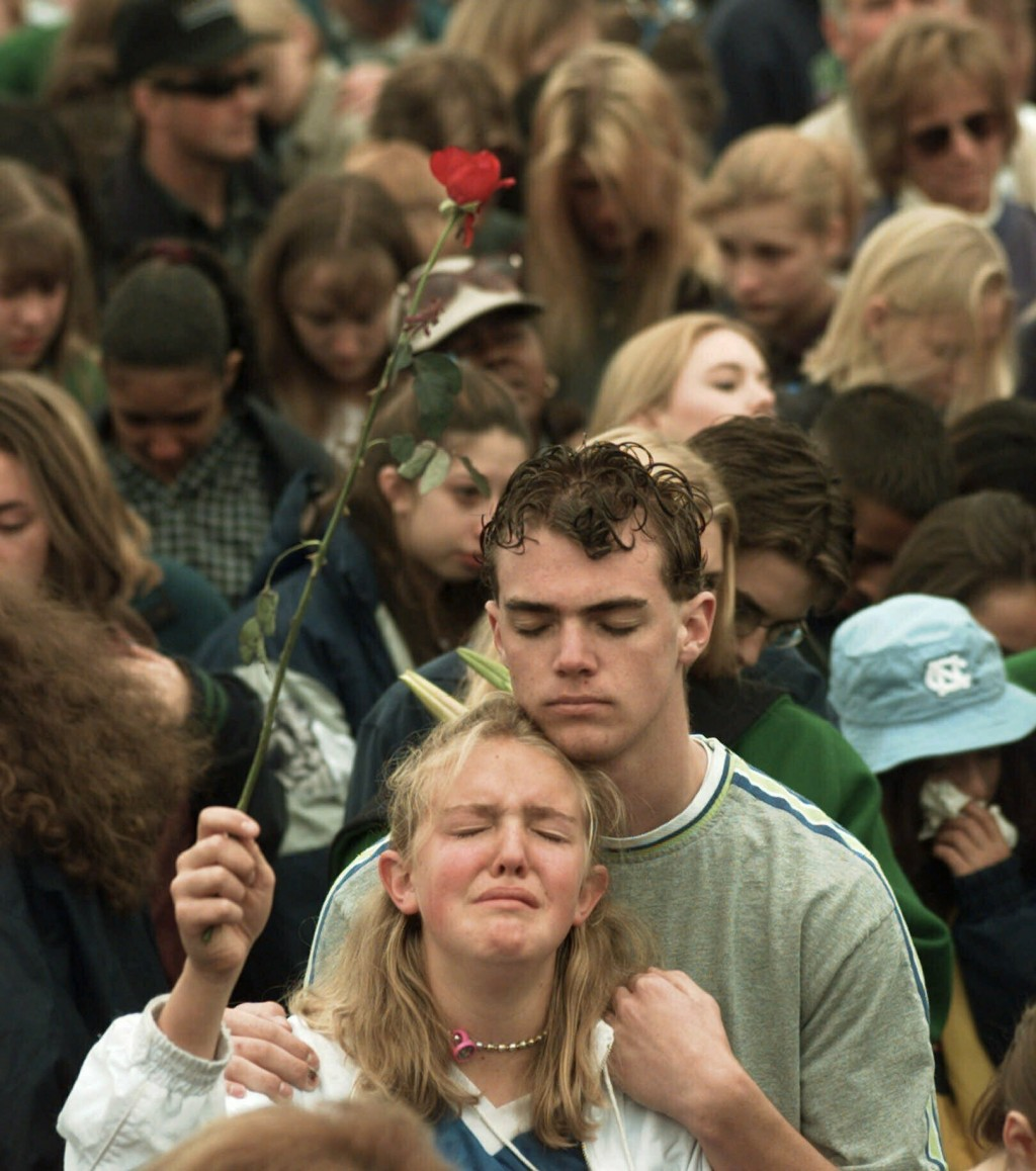 FILE - In this April 25, 1999, file photo, a young girl holds a rose as she is held during a prayer at a memorial service on for the victims of the Co