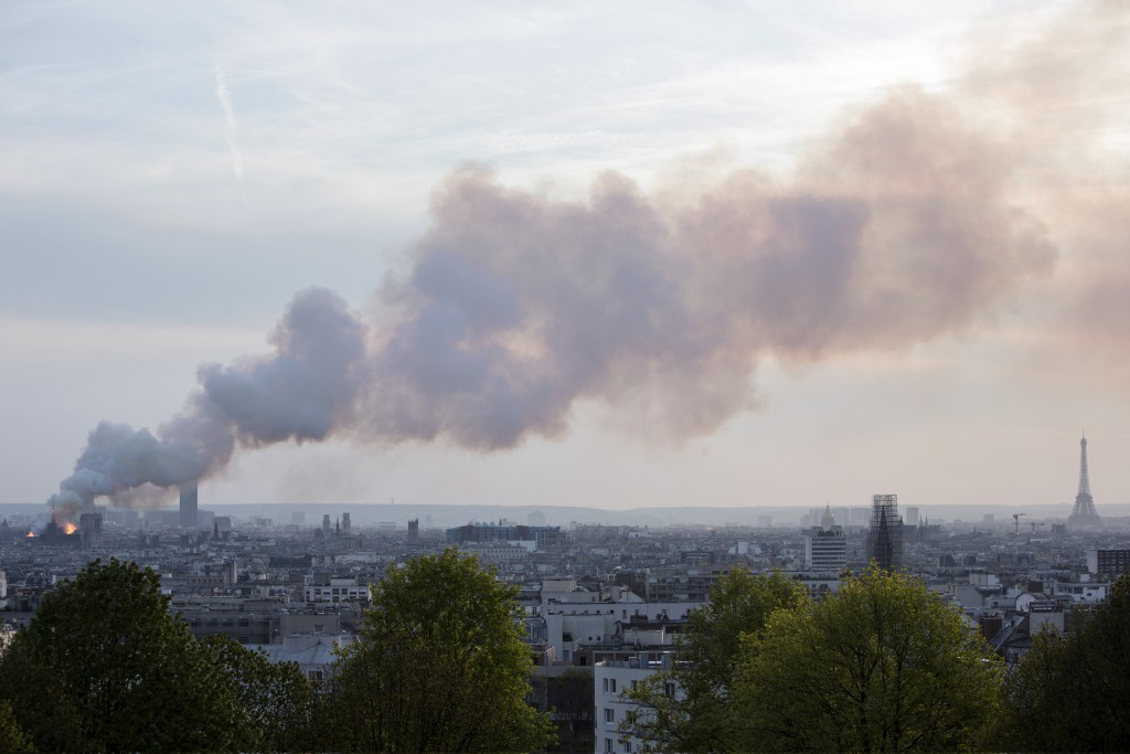 Smoke fill the air as Notre Dame cathedral is burning in Paris, Monday, April 15, 2019. Massive plumes of yellow brown smoke is filling the air above