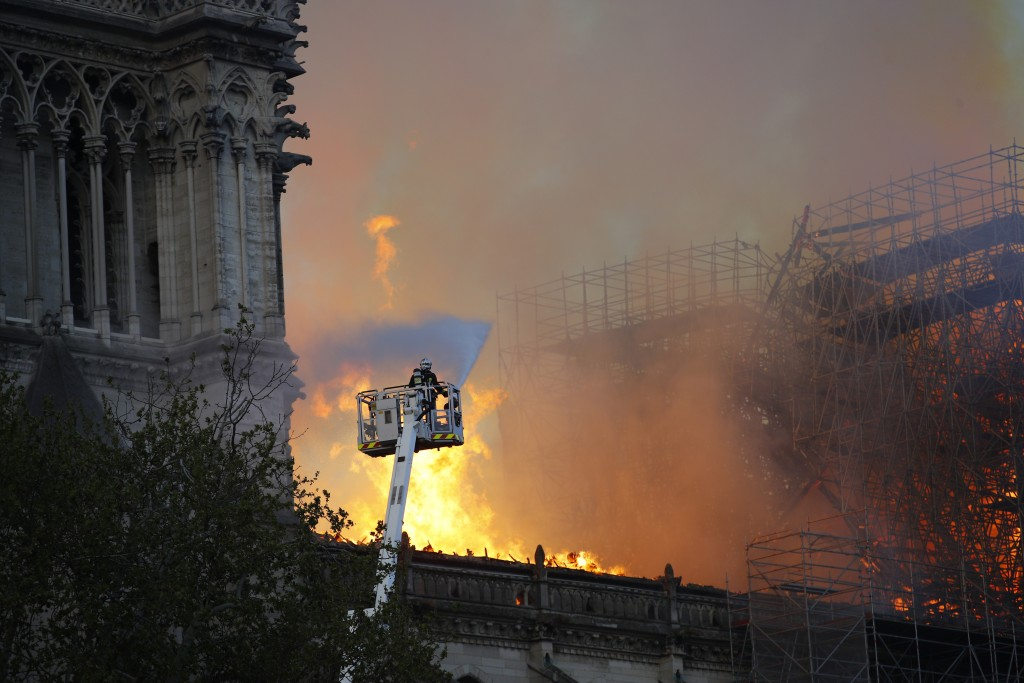 A firefighter uses a hose as Notre Dame cathedral burns in Paris, Monday, April 15, 2019. A catastrophic fire engulfed the upper reaches of Paris' soa