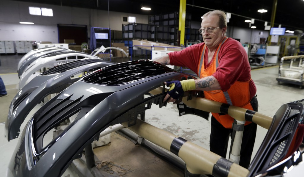 FILE - This Nov. 28, 2018 file photo shows Clifford Goff, a bezel assembler, transferring a front end of a General Motors Chevrolet Cruze during assem