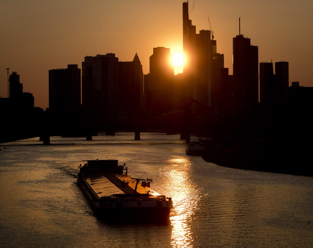 A cargo shop is seen on the river Main as the sun sets behind the bank buildings in Frankfurt, Germany, Monday, April 15, 2019. (AP Photo/Michael Prob...