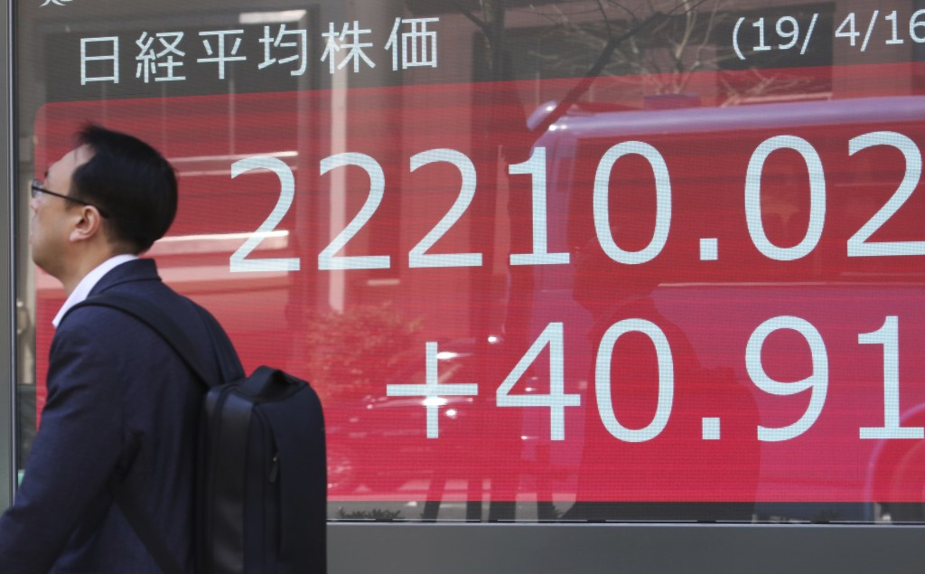 A man walks by an electronic stock board of a securities firm in Tokyo, Tuesday, April 16, 2019.  Shares were mixed Tuesday in Asia in mostly narrow t