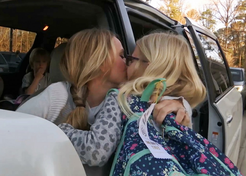 In this Wednesday, March 27, 2019, frame from video, Kacey Ruegsegger Johnson kisses her daughter, Logan, as she drops her off at her school in Cary, ...