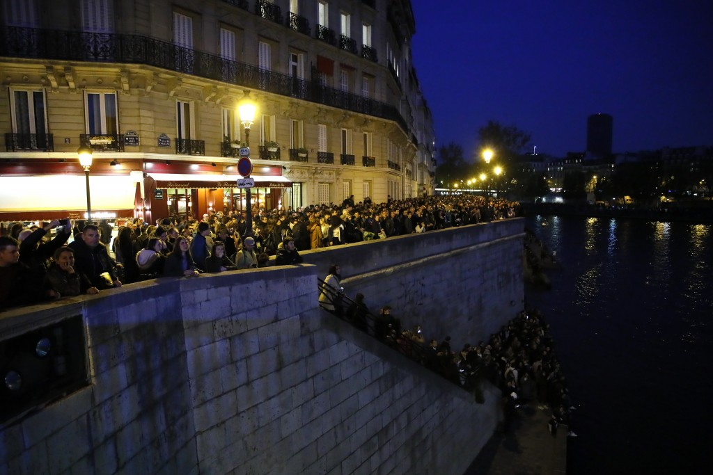 People watch Notre Dame cathedral burning from the Seine river banks in Paris, Monday, April 15, 2019. A catastrophic fire engulfed the upper reaches