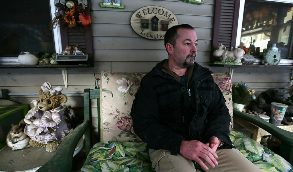 In this Thursday, March 7, 2019 photo, former SWAT officer Al Joyce sits on the porch at his mother's home in Otisfield, Maine. Joyce left his job in