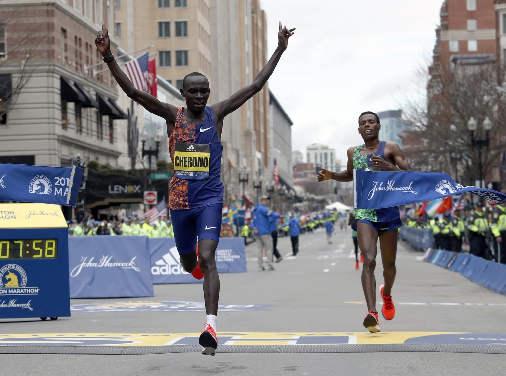 Lawrence Cherono, of Kenya, breaks the tape to win the 123rd Boston Marathon in front of Lelisa Desisa, of Ethiopia, right, on Monday, April 15, 2019,