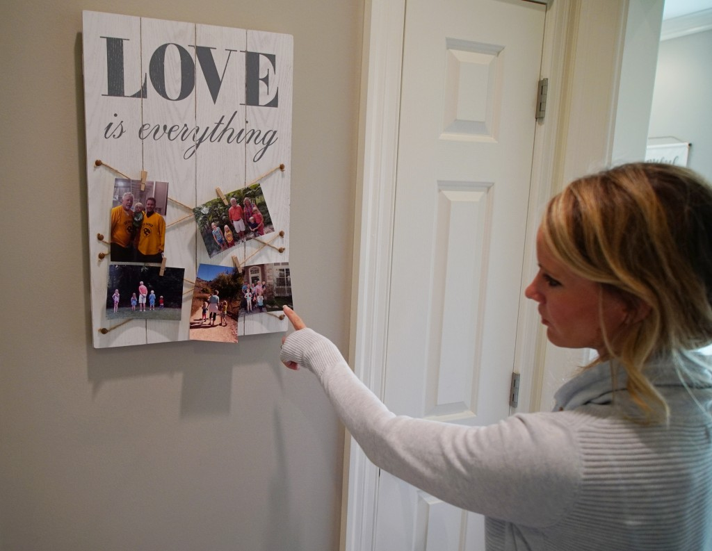 In this Wednesday, March 27, 2019, photo, Kacey Ruegsegger Johnson looks at photos of her family at her home in Cary, N.C. Ruegsegger Johnson survived
