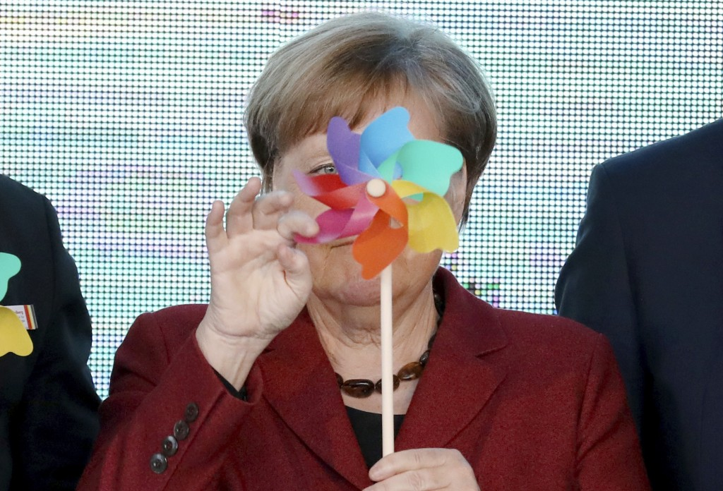 German Chancellor Angela Merkel holds an toy windmill, during an event officially launching an offshore wind park in the Baltic Sea near the island Ru