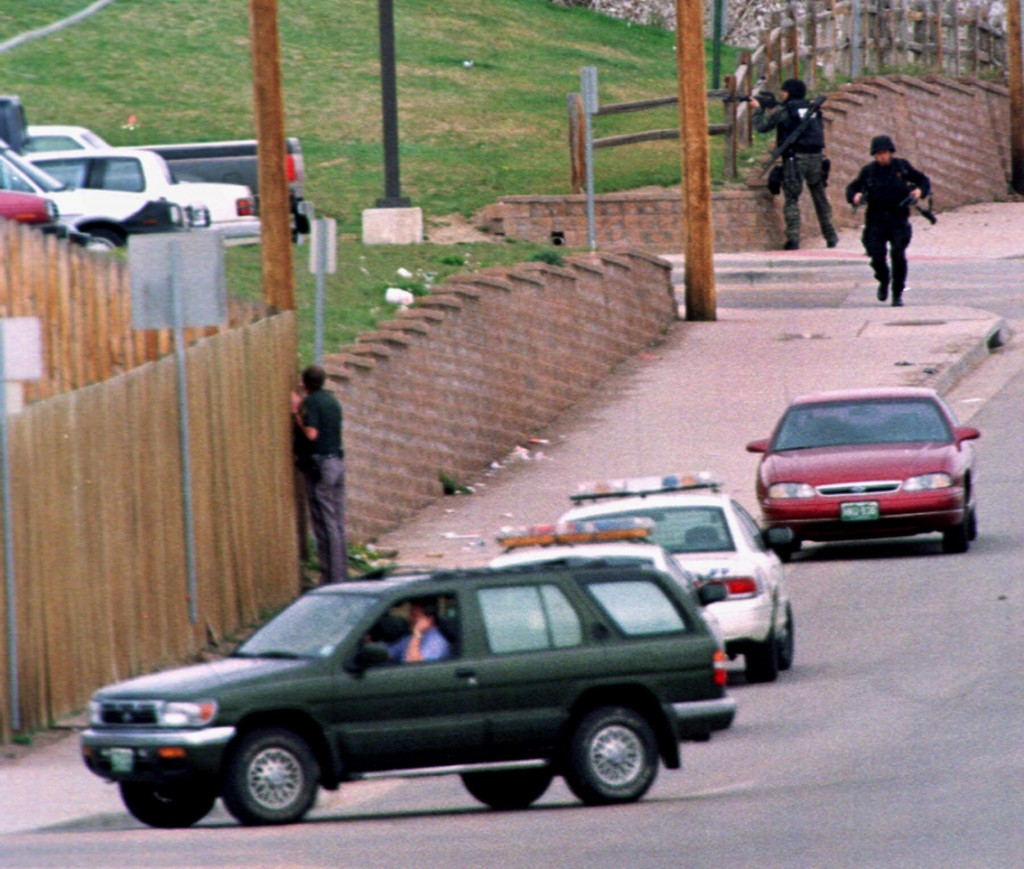 FILE - In this April 20, 1999, file photo, SWAT members run down Pierce Street while a Jefferson County, Colo., Sheriff's Department deputy peers thro