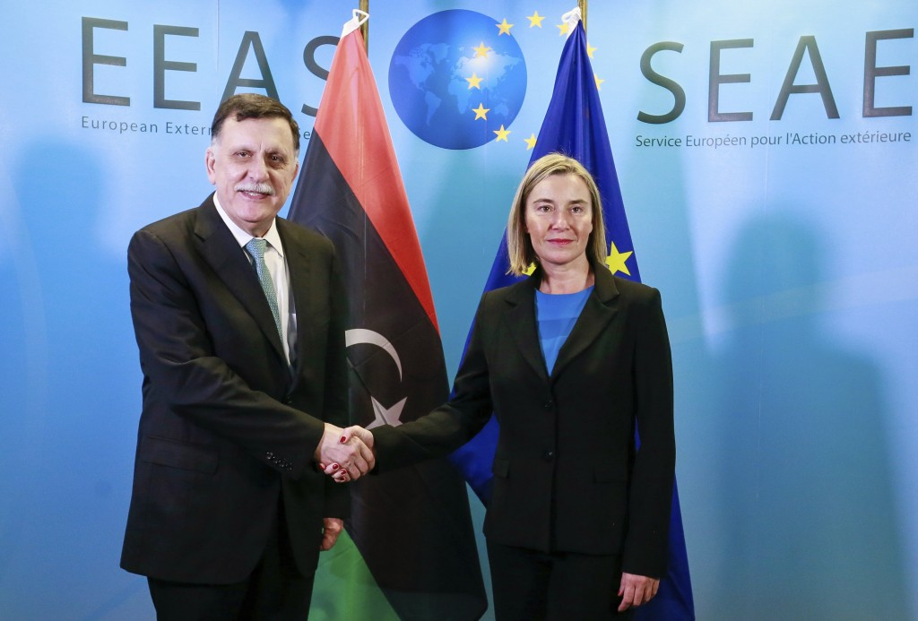 FILE - In this Dec. 4, 2018 file photo, Prime Minister of Libya Fayez al-Sarraj, left, is welcomed by EU foreign policy chief Federica Mogherini for a