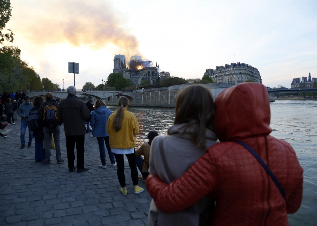 People watch as flames and smoke rise from Notre Dame cathedral as it burns in Paris, Monday, April 15, 2019. Massive plumes of yellow brown smoke is ...