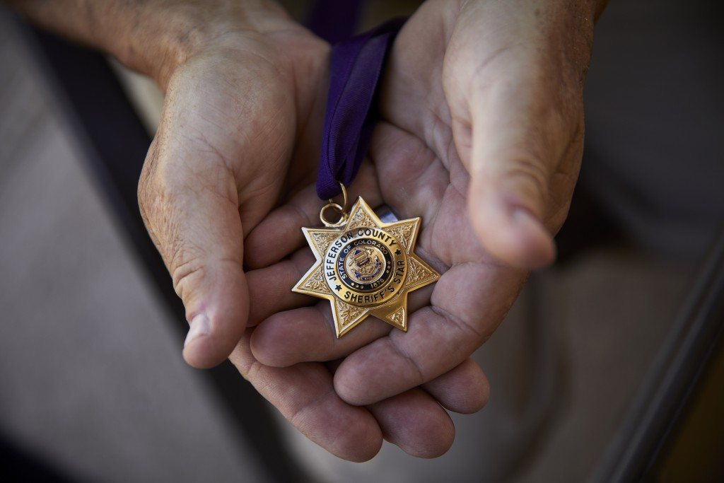 In this April 9, 2019, photo, Grant Whitus holds the Jefferson County Sheriff's Star at his home in Lake Havasu City, Ariz. Whitus received the award ...