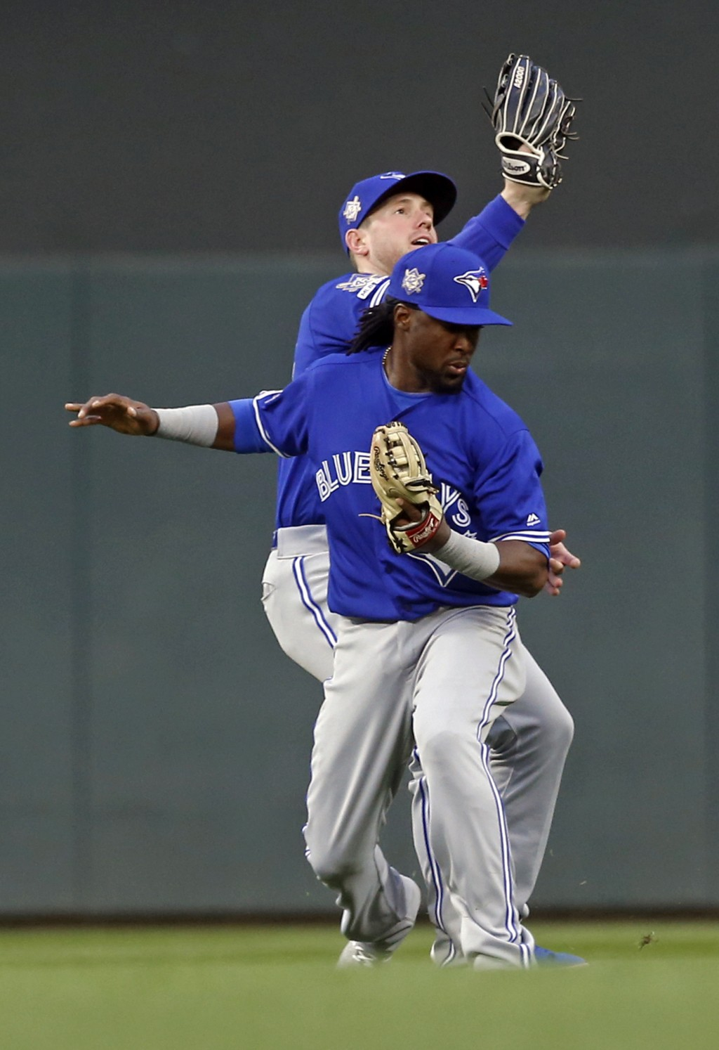 Toronto Blue Jays right fielder Billy McKinney, rear, catches a fly ball by Minnesota Twins' Mitch Garver after colliding with second baseman Alan Han