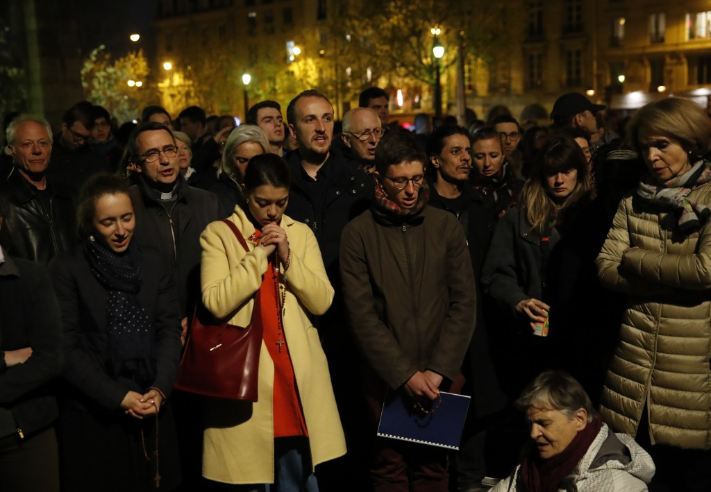 People pray as Notre Dame cathedral is burning in Paris, Monday, April 15, 2019. A catastrophic fire engulfed the upper reaches of Paris' soaring Notr