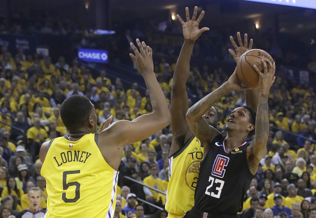 Los Angeles Clippers guard Lou Williams (23) shoots against Golden State Warriors center Kevon Looney (5) and forward Draymond Green during the first