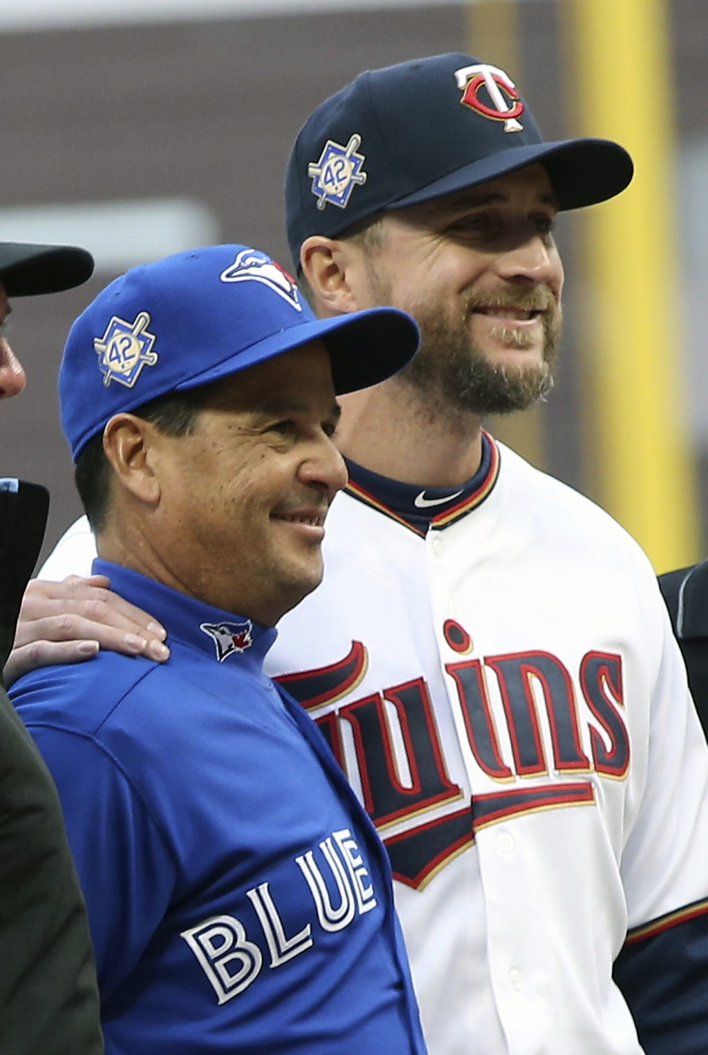 Toronto Blue Jays manager Charlie Montoya, left, and Minnesota Twins manager Rocco Baldelli pose with umpires before a baseball game Monday, April 15,