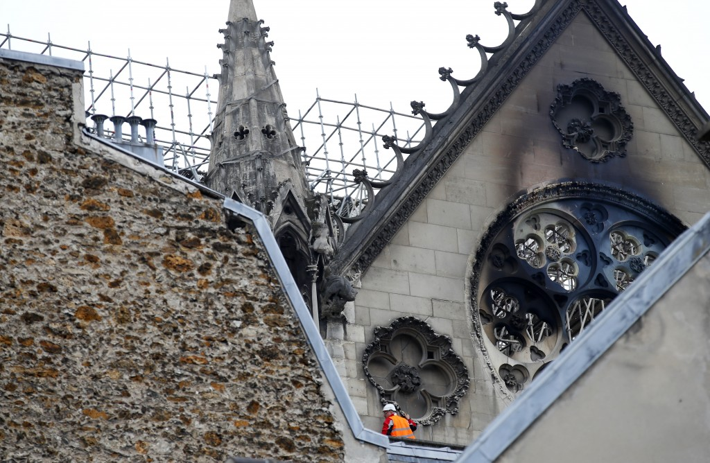 A man is pictured near chared glass windows Notre Dame cathedral Tuesday April 16, 2019 in Paris. Firefighters declared success Tuesday in a more than