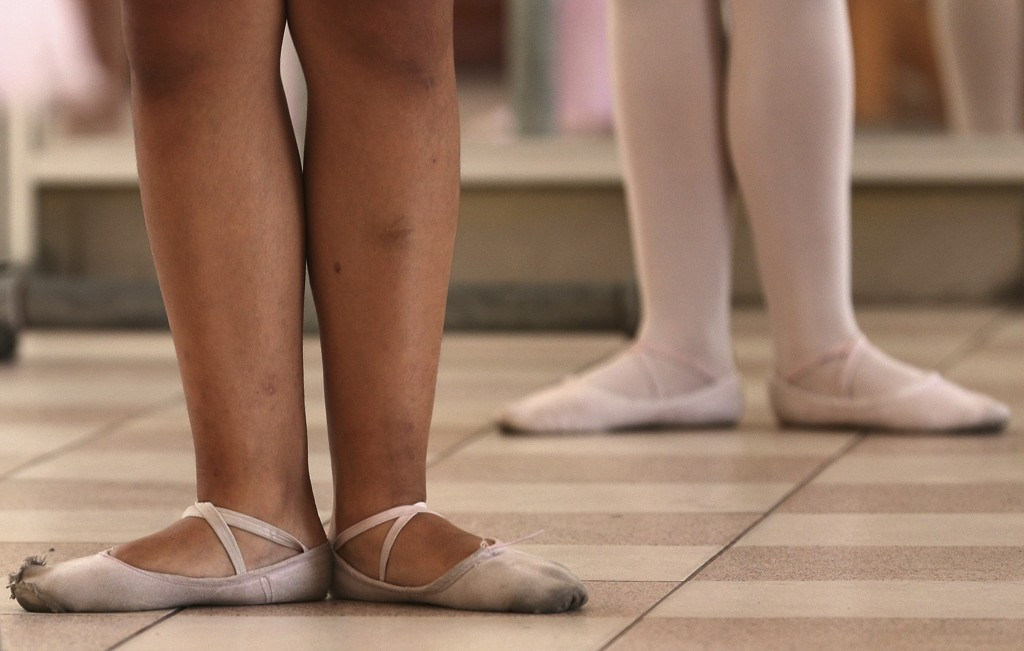 In this April 2, 2019 photo, young ballet students stand in first position in a dance studio at a public school in the Chorrillos neighborhood, a poor