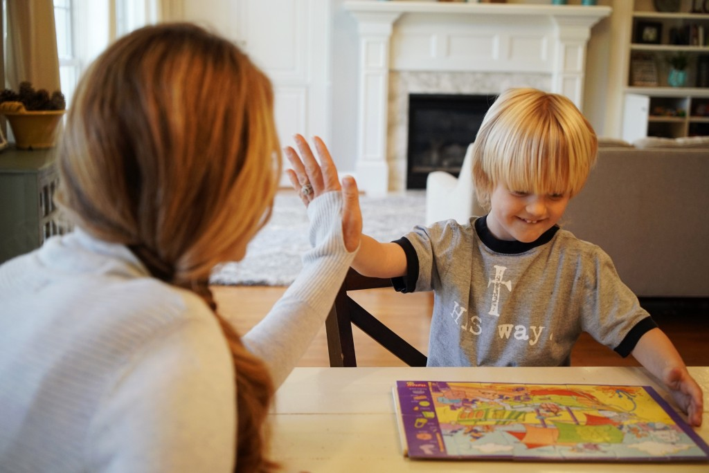 In this Wednesday, March 27, 2019, photo, Kacey Ruegsegger Johnson high-fives with her son Corban as they finish a puzzle in their Cary, N.C., home. T...