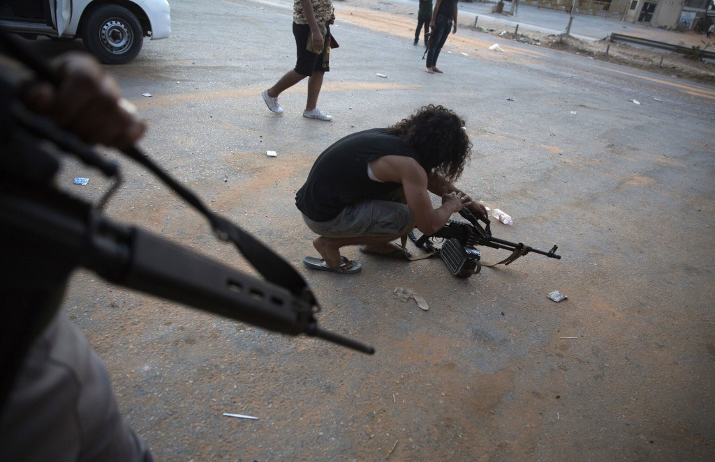 FILE - In this Sept. 21, 2018 file photo, a fighter under the UN-backed government prepares his gun during clashes in southern Tripoli, Libya. Various