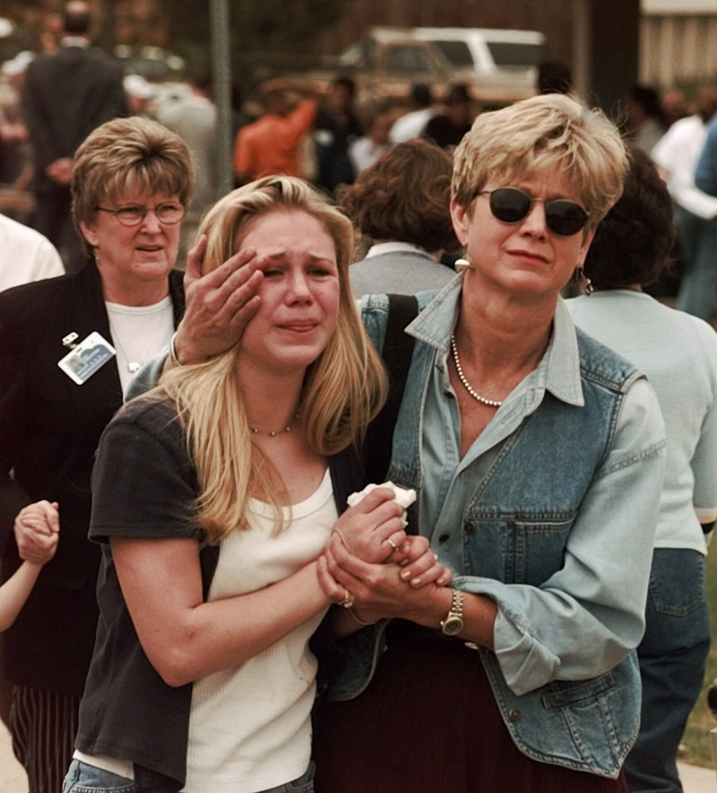 FILE - In this April 20, 1999, file photo, Fran Allison, right, comforts her daughter Brooke after they were reunited after a shooting at Columbine Hi