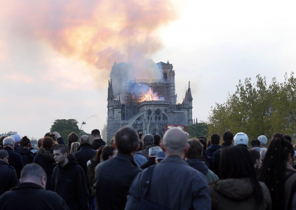 People watch as flames and smoke rise from Notre Dame cathedral as it burns in Paris, Monday, April 15, 2019. Massive plumes of yellow brown smoke is