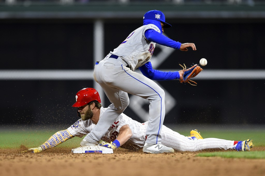 Philadelphia Phillies' Bryce Harper, bottom, slides into second base safely past New York Mets' Amed Rosario after Harper hit an RBI single off Noah S