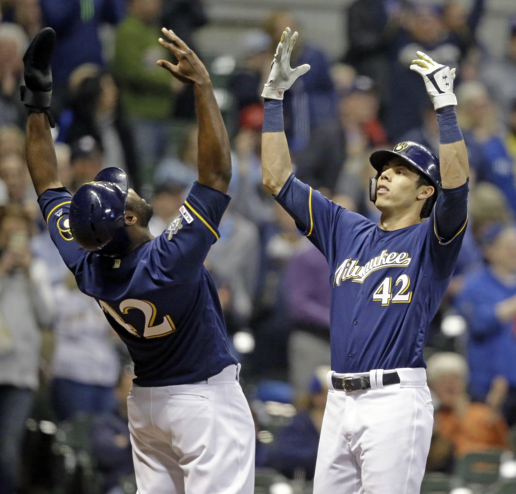 Milwaukee Brewers' Christian Yelich, right, reacts with Lorenzo Cain after hitting a three-run home run against the St. Louis Cardinals during the six