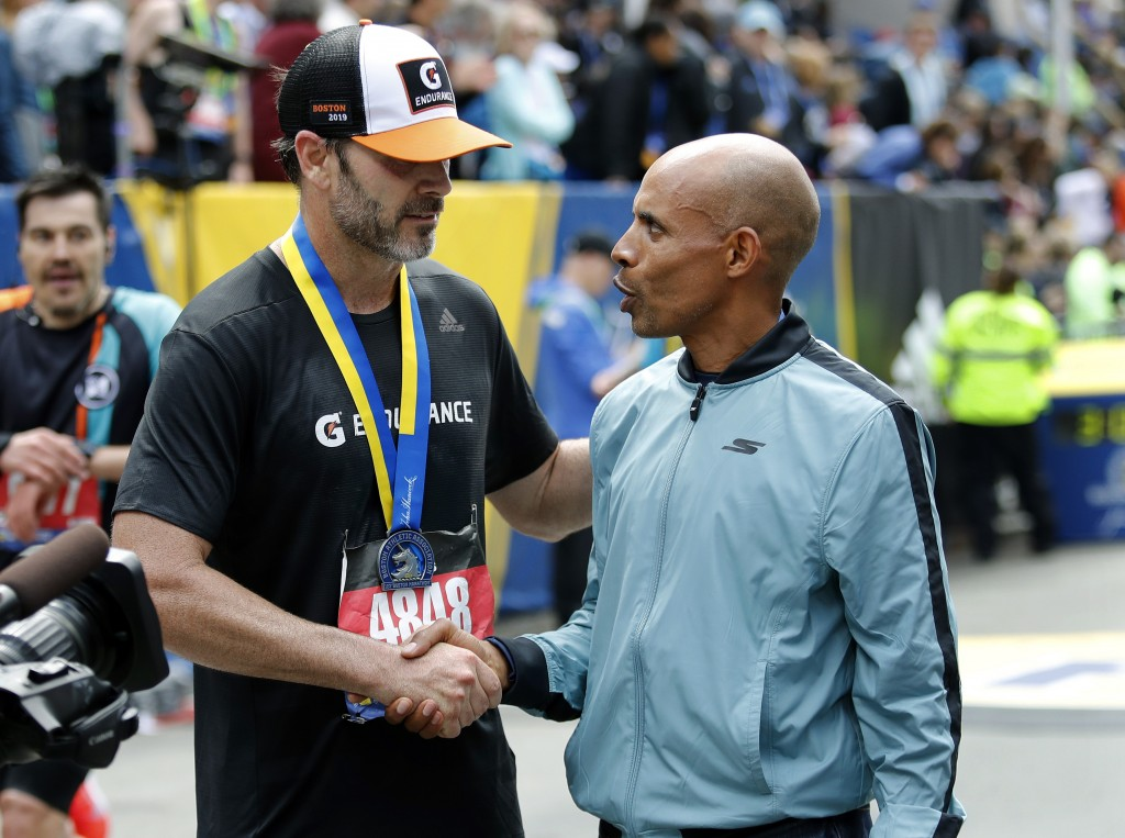 NASCAR driver Jimmie Johnson, left, of Charlotte, shakes hands with grand marshall Meb Keflezighi, of San Diego, after finishing the 123rd Boston Mara