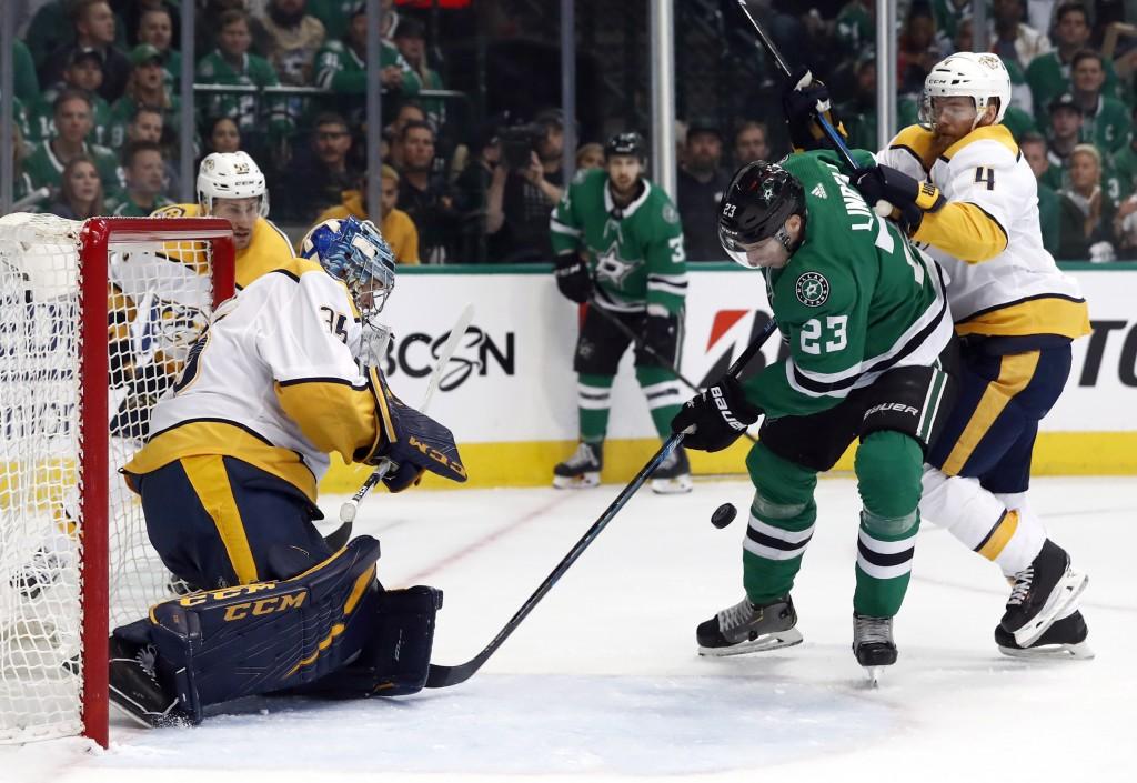 Nashville Predators goaltender Pekka Rinne (35) gets help from defenseman Ryan Ellis (4) while defending the net against pressure from Dallas Stars de