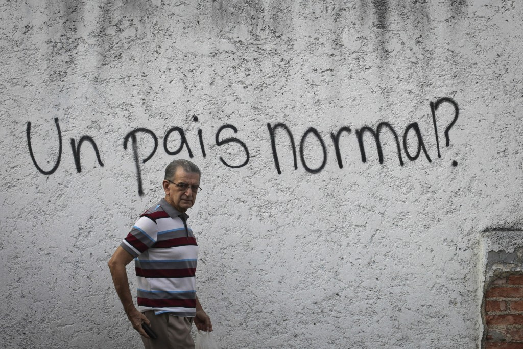 """Graffiti that asks in Spanish """"A normal country?"""" covers a wall in the middle-class neighborhood of Alta Florida in Caracas, Venezuela, Monday, April"""