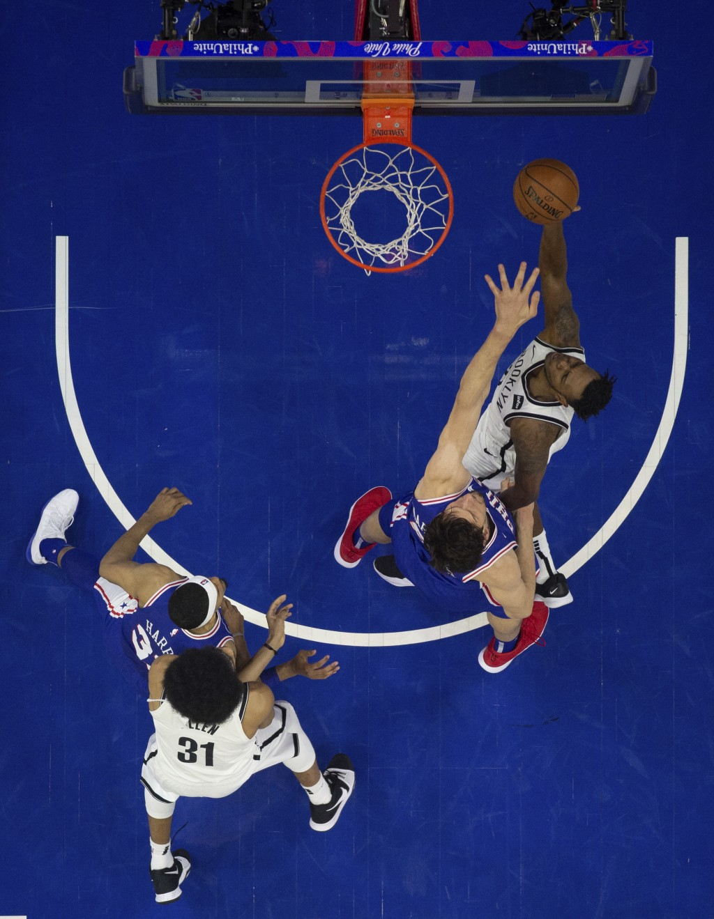 Brooklyn Nets' Treveon Graham, right, goes up for the shot against Philadelphia 76ers' Boban Marjanovic, center right, of Serbia, during the first hal...