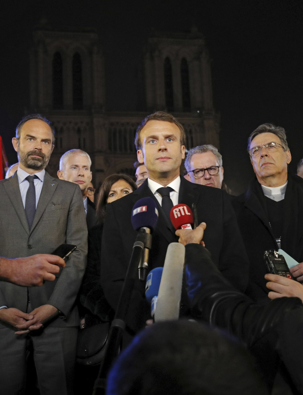 French Prime Minister Edouard Philippe, left, French President Emmanuel Macron, and Archbishop of Paris, Michel Aupetit, right, answer reporters after...