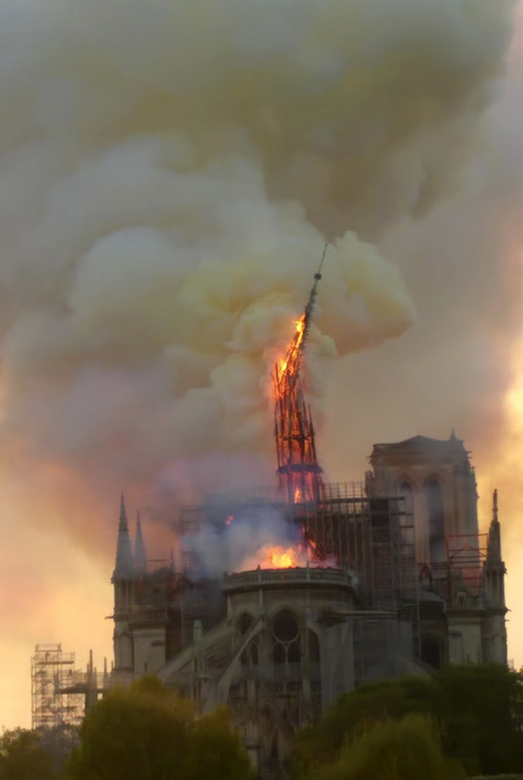 Flames and smoke rise as the spire of Notre Dame cathedral collapses in Paris, Monday, April 15, 2019. A catastrophic fire engulfed the upper reaches