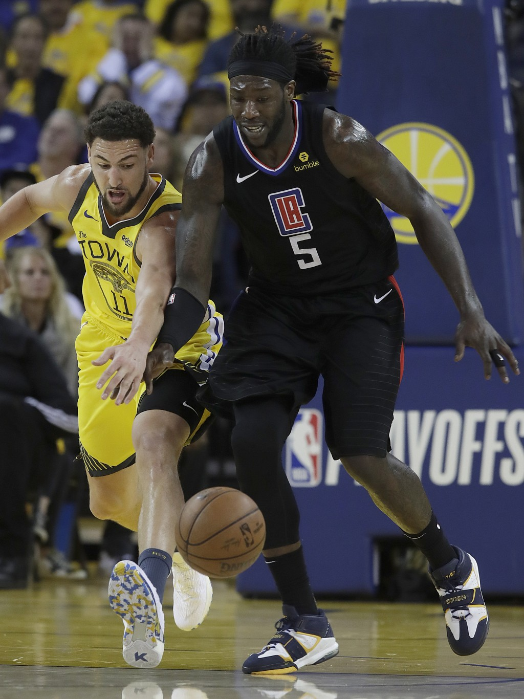 Golden State Warriors guard Klay Thompson, left, and Los Angeles Clippers forward Montrezl Harrell (5) go after a loose ball during the first half of