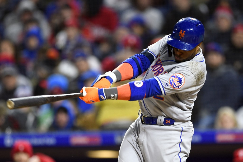 New York Mets' Robinson Cano follows through after hitting a two-run double off Philadelphia Phillies' Aaron Nola during the fourth inning of a baseba
