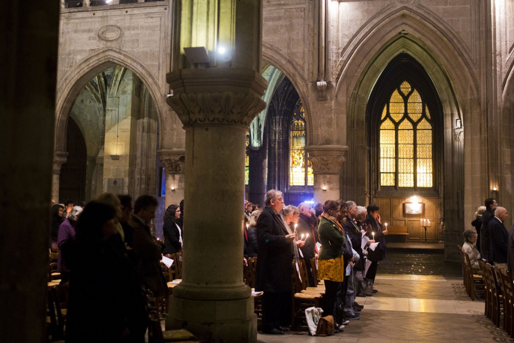 This handout photo taken by Evgeny Feldman on Saturday, April 19, 2014, shows people holing candles inside Notre-Dame-cathedral in Paris, France. As w