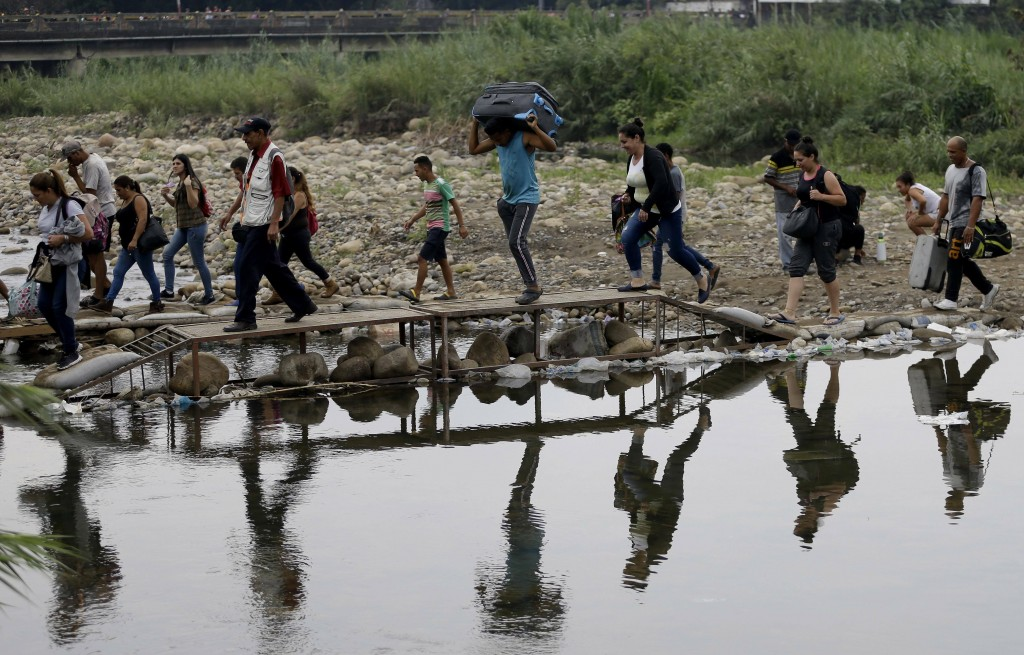 FILE - In this April 14, 2019 file photo, Venezuelans cross illegally into Colombia near the Simon Bolivar International Bridge, top, which is partial