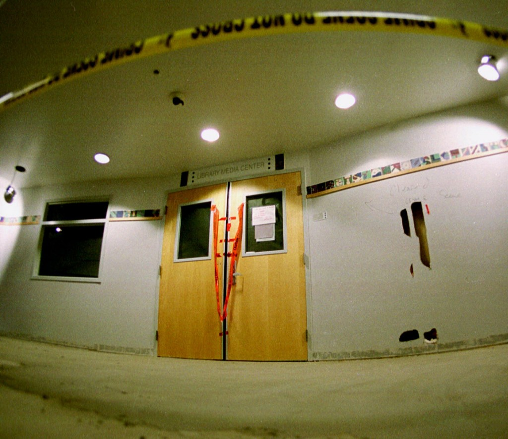 FILE - In this June 15, 1999, file photo, tape marks the line in front of the doors to the library in Columbine High School as members of the media to