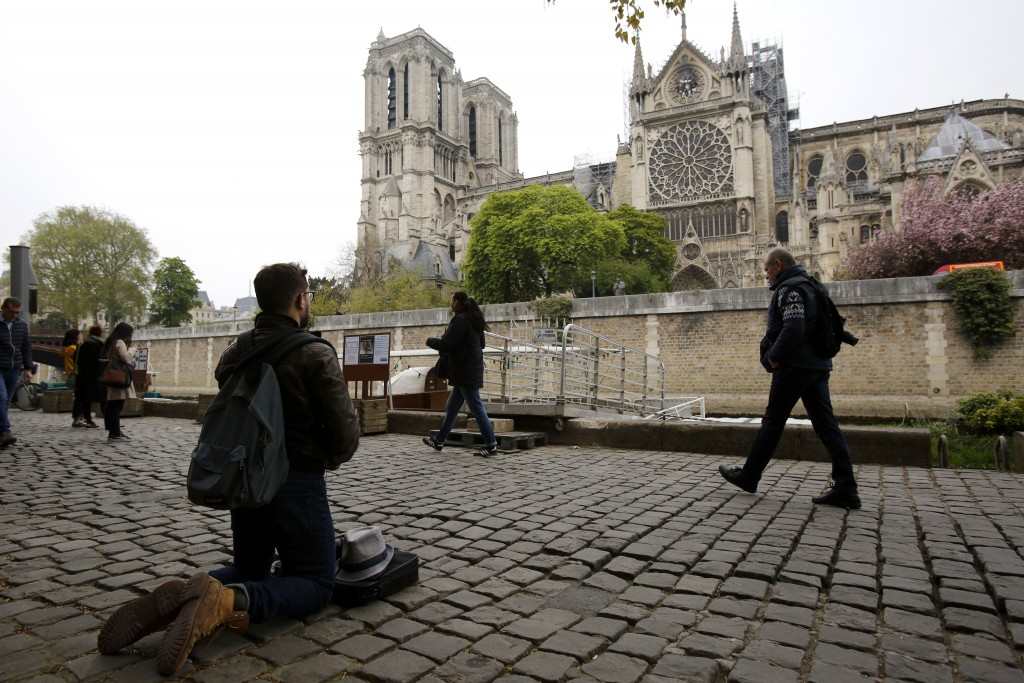 Man kneels as people came to watch and photograph the Notre Dame cathedral after the fire in Paris, Tuesday, April 16, 2019. Experts are assessing the