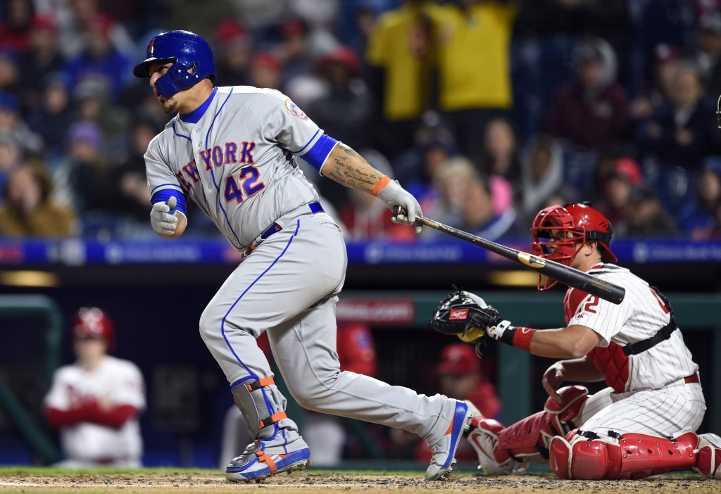 New York Mets' Wilson Ramos, left, watches the ball in front of Philadelphia Phillies' J.T. Realmuto after hitting a two-run single off Aaron Nola dur