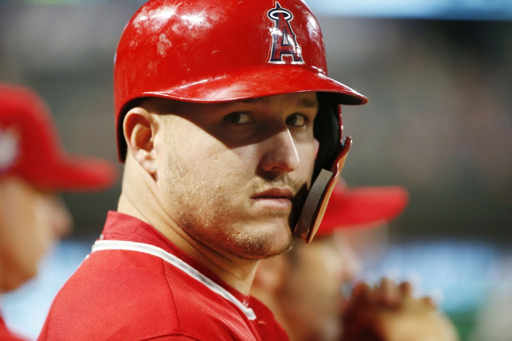 Los Angeles Angels designated hitter Mike Trout looks from the dugout as he waits to bat against the Texas Rangers during the eighth inning of a baseb...