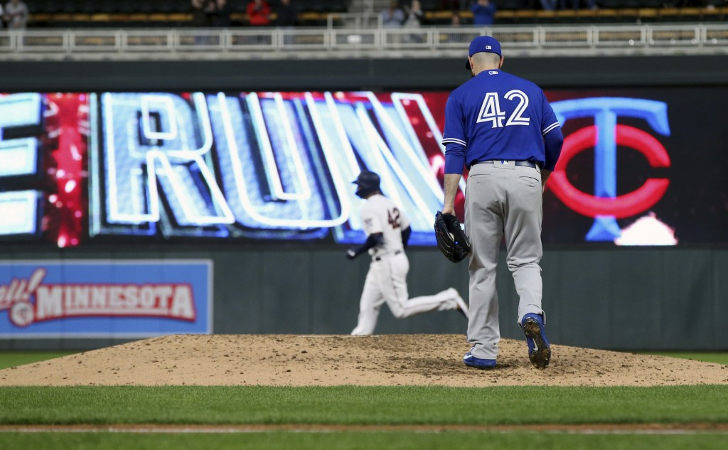 Toronto Blue Jays pitcher Matt Shoemaker, right, returns to the mound as Minnesota Twins' C.J. Cron rounds the bases on a three-run home run in the fo