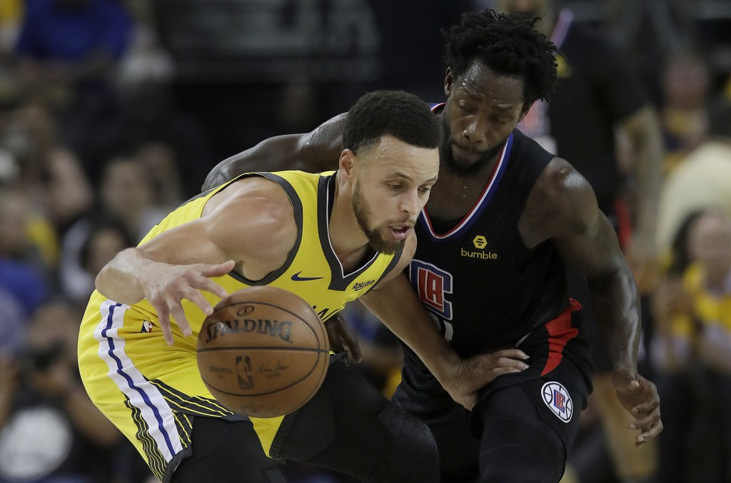 Golden State Warriors guard Stephen Curry, left, is defended by Los Angeles Clippers guard Patrick Beverley during the first half of Game 2 of a first
