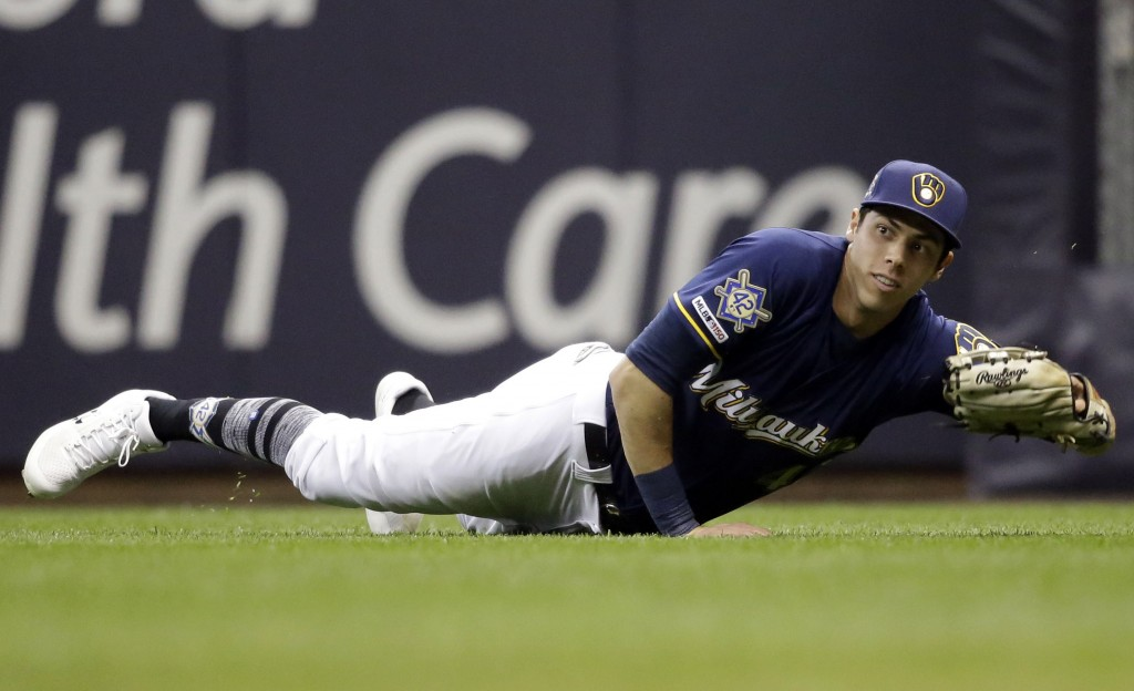 Milwaukee Brewers' Christian Yelich makes a diving catch on a ball hit by St. Louis Cardinals' Kolten Wong during the seventh inning of a baseball gam