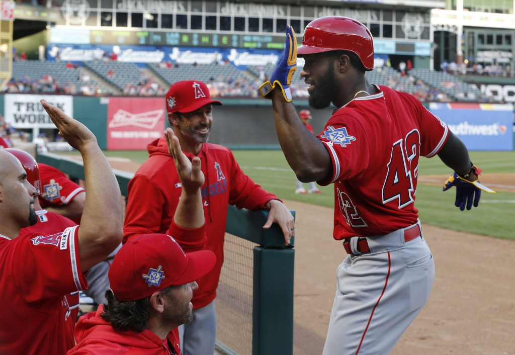 Los Angeles Angels' Brian Goodwin, right, is congratulated after hitting a two-run home run against the Texas Rangers during the first inning of a bas...