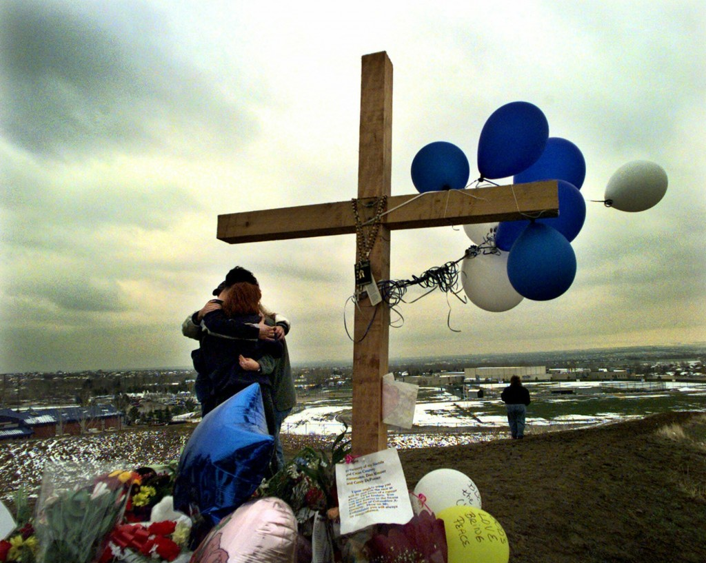 FILE - In this April 24, 1999, file photo, students embrace each other at a makeshift memorial for their slain classmates at Columbine High School on