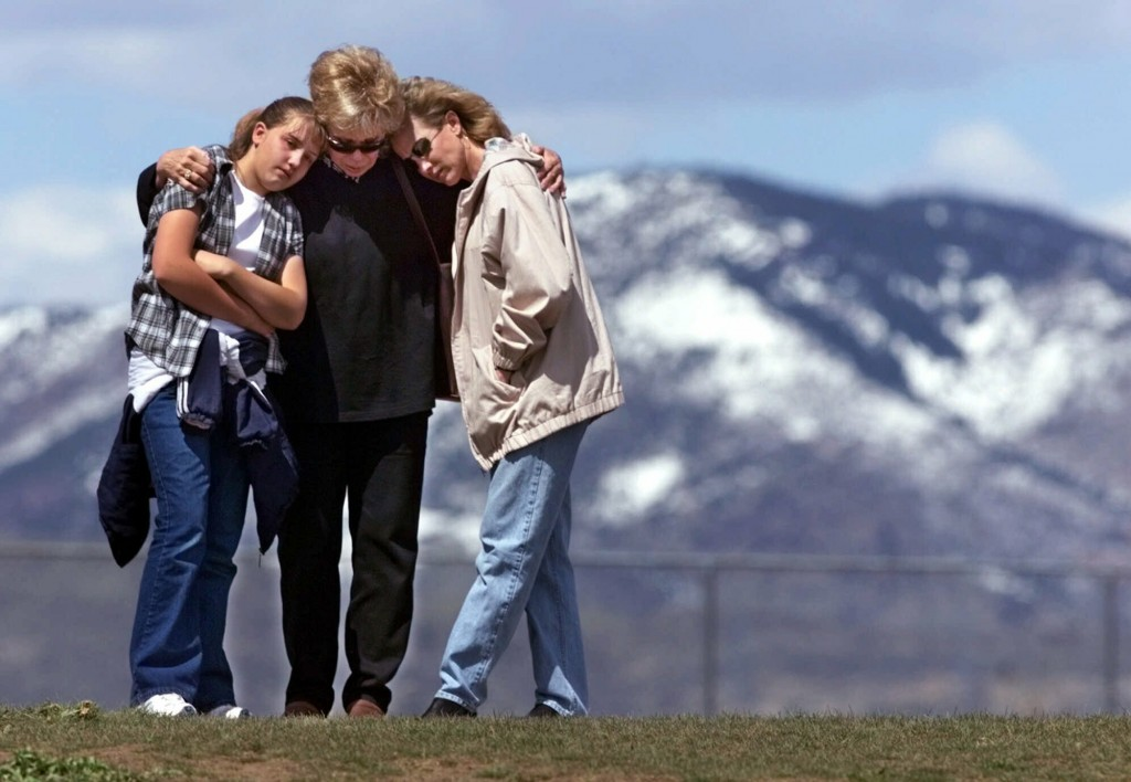 FILE - In this April 27, 1999, file photo, Krista Sleeth, Bev Fleer and Cindy Sleeth embrace while standing on a hill above Columbine High School in L