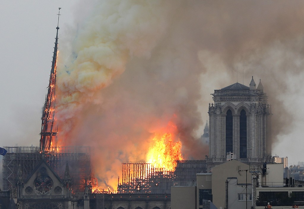 Flames rise from Notre Dame cathedral as it burns in Paris, Monday, April 15, 2019. Massive plumes of yellow brown smoke is filling the air above Notr